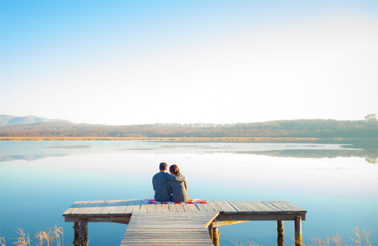 Photo of couple sitting on a dock