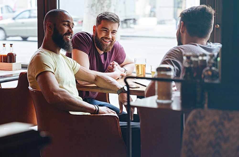 Photo of three men having a conversation in a restaurant