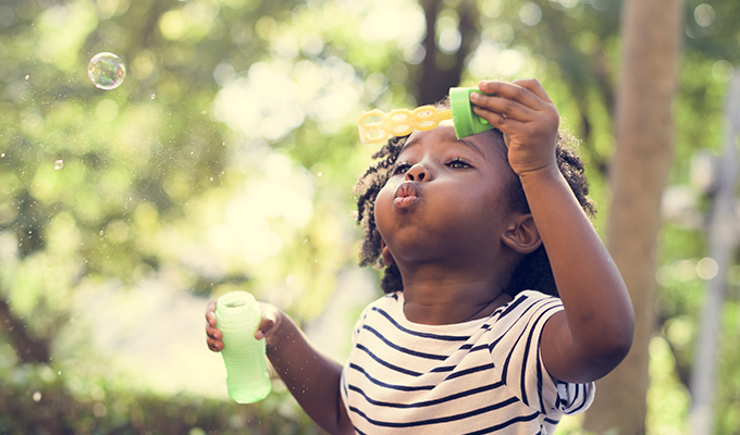 Photo of a young girl blowing bubbles