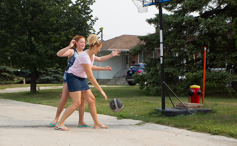 Photo of Nealla McKie and her mom Jocelyn playing a game of one-on-one basketball