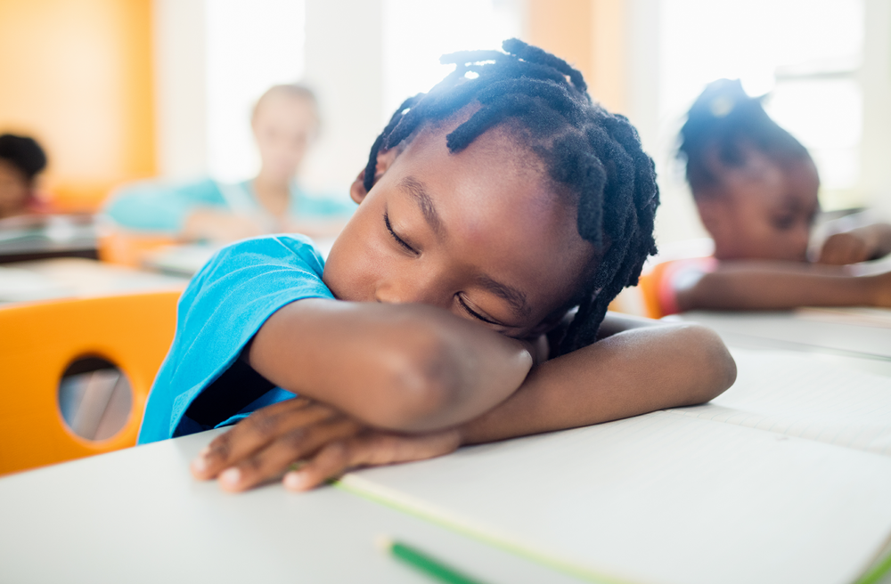 Photo of a child falling asleep at his desk in classroom