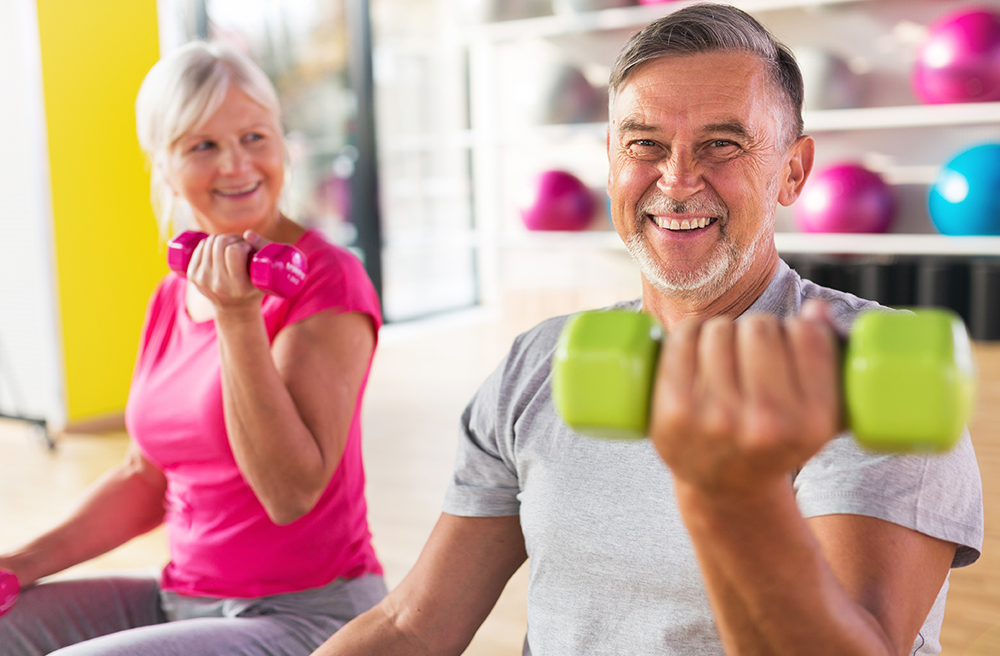 Photo of two middle aged people lifting weights