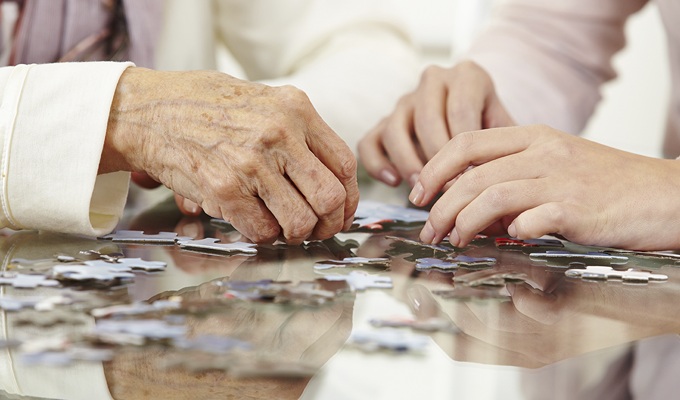 Photo of an elderly woman doing a puzzle with a younger woman