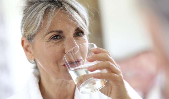 Photo of a woman drinking a glass of water