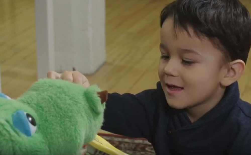 Photo of an Indigenous child learning to brush teeth on a stuffed toy